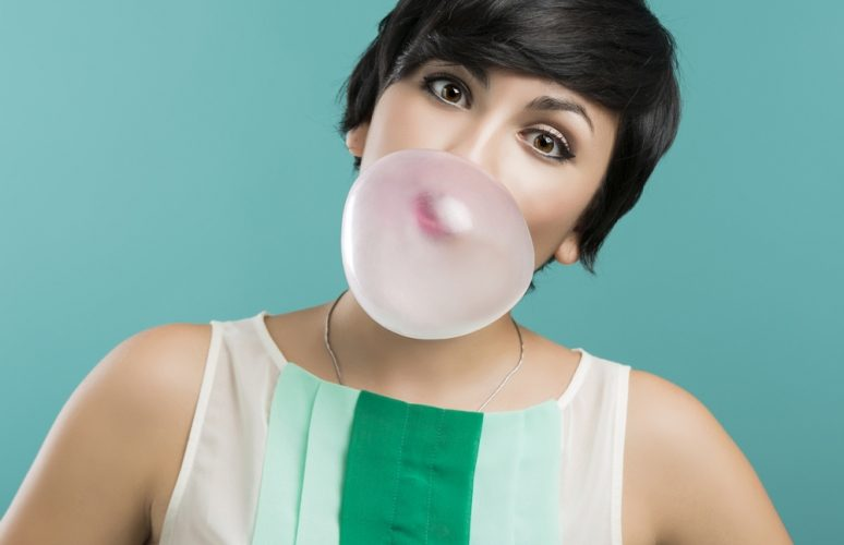 Woman with a chewing gum baloon